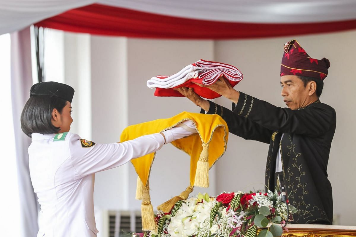 President Joko presenting the national flag to a student at the Istana Merdeka presidential palace in Jakarta. She then carried it to the palace's front yard where it was hoisted.
