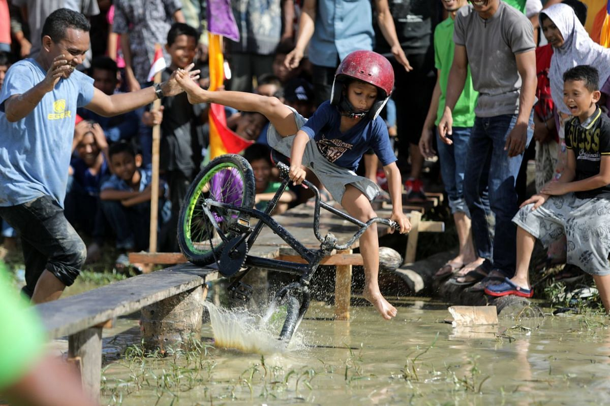 A young boy in Banda Aceh losing his balance as he took part in a game where participants had to manoeuvre their bikes on narrow boards placed over water.