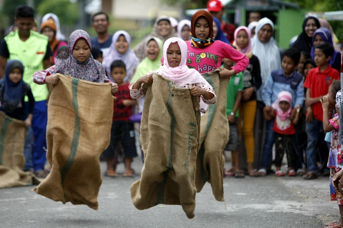 Indonesian students competing in a sack race in Banda Aceh on Aug 17.
