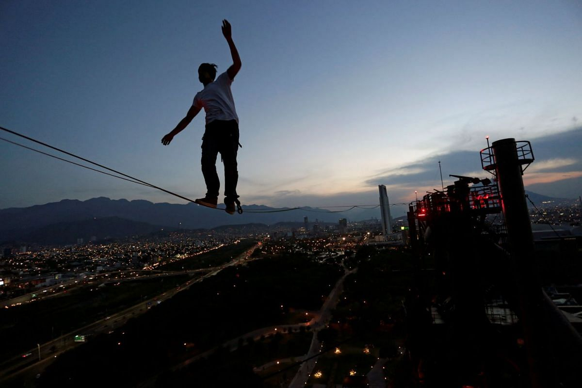 A slackliner crosses a high wire between two chimneys of the structure housing former foundry Horno Alto No. 3, at Fundidora park in Monterrey, Mexico.