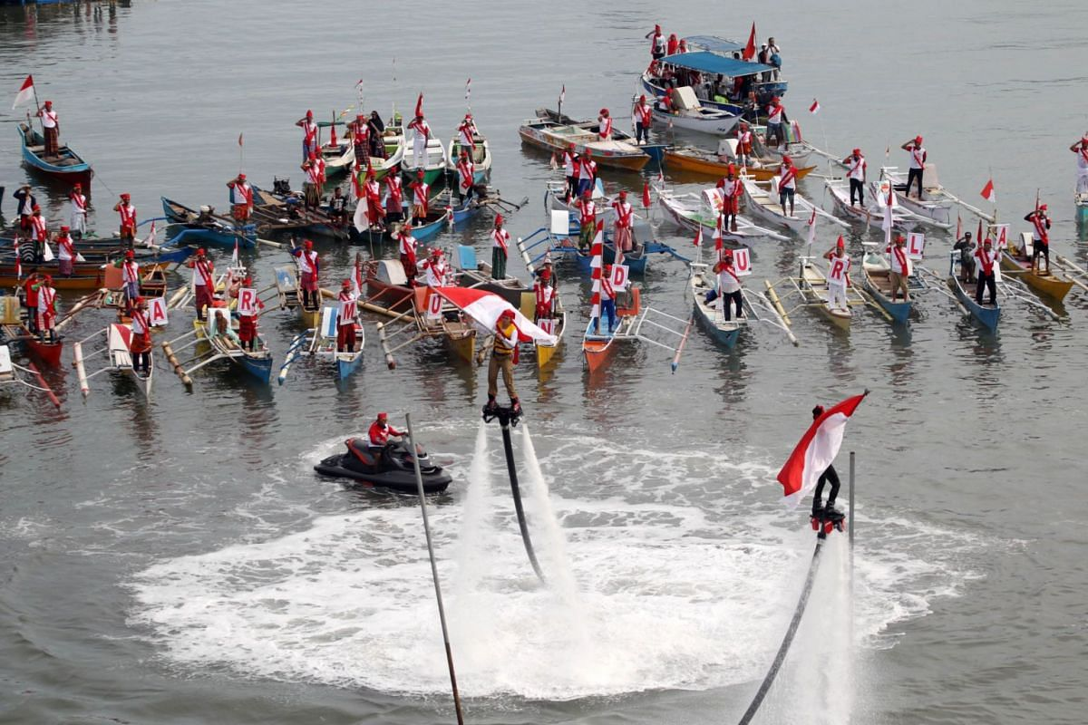 Contestants on water-powered Flyboards attempting to put flags on poles in Makassar, South Sulawesi, on Aug 17.