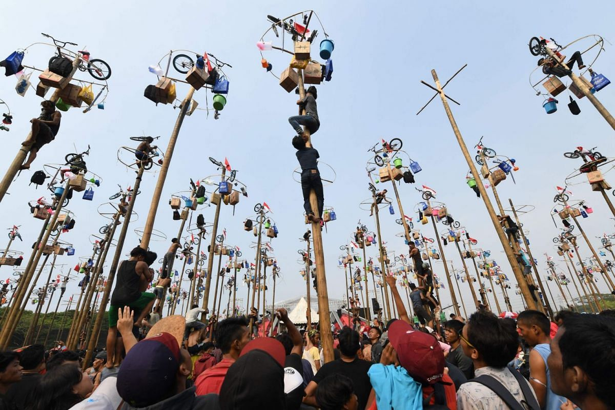 Participants at Ancol beach in Jakarta taking part in Panjat Pinang, a pole-climbing contest that dates back to Dutch colonial days. It involves teams of four trying to climb greased poles to get the prizes hung at the top.