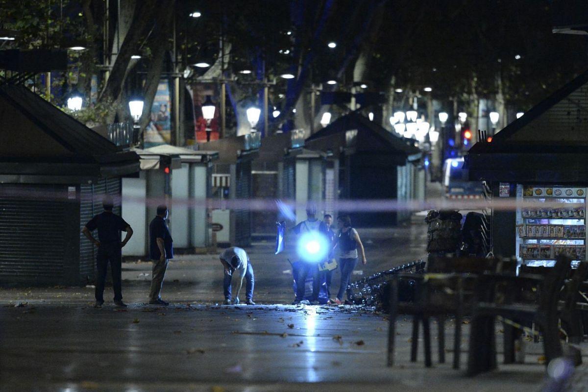 Policemen check the area after towing away the van which ploughed into the crowd, killing at least 13 people and injuring around 100 others on the Rambla in Barcelona, on Aug 18, 2017.A driver deliberately rammed a van into a crowd on Barcelona's mos