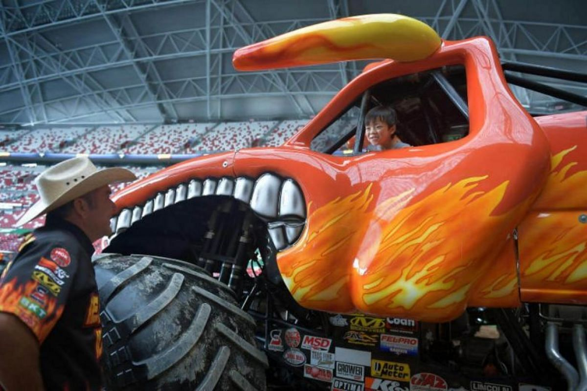 Yang Ewan, five, tries out Marc McDonald's (left) monster truck during a media preview at the National Stadium on Aug 18, 2017.