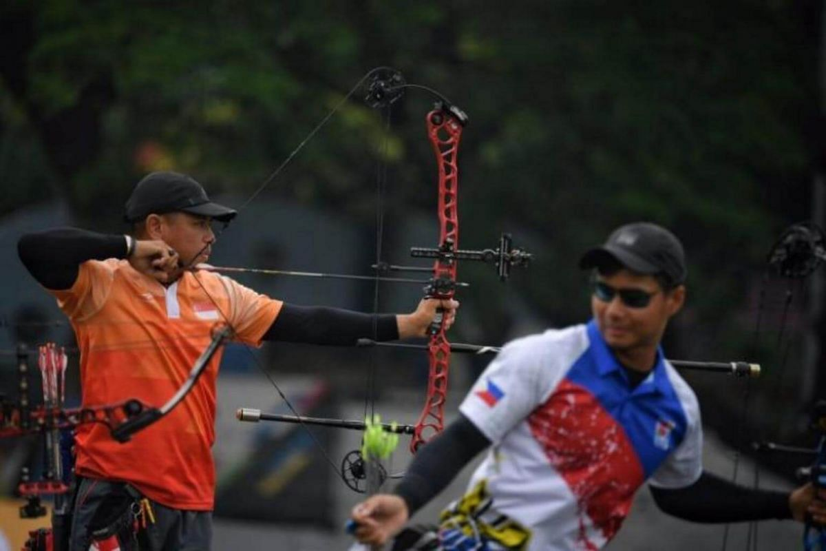 Singaporean archer Alan Lee (left) in action during the semi-finals of the SEA Games compound men's team event held at the National Sports Centre on Aug 17, 2017.