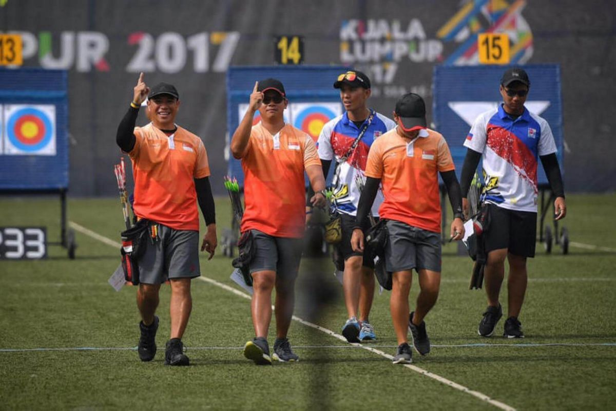 Singaporean archers (from left) Alan Lee, Pang Toh Jin and Ang Han Teng gesture after making the finals of the SEA Games compound men's team event on Aug 17, 2017.