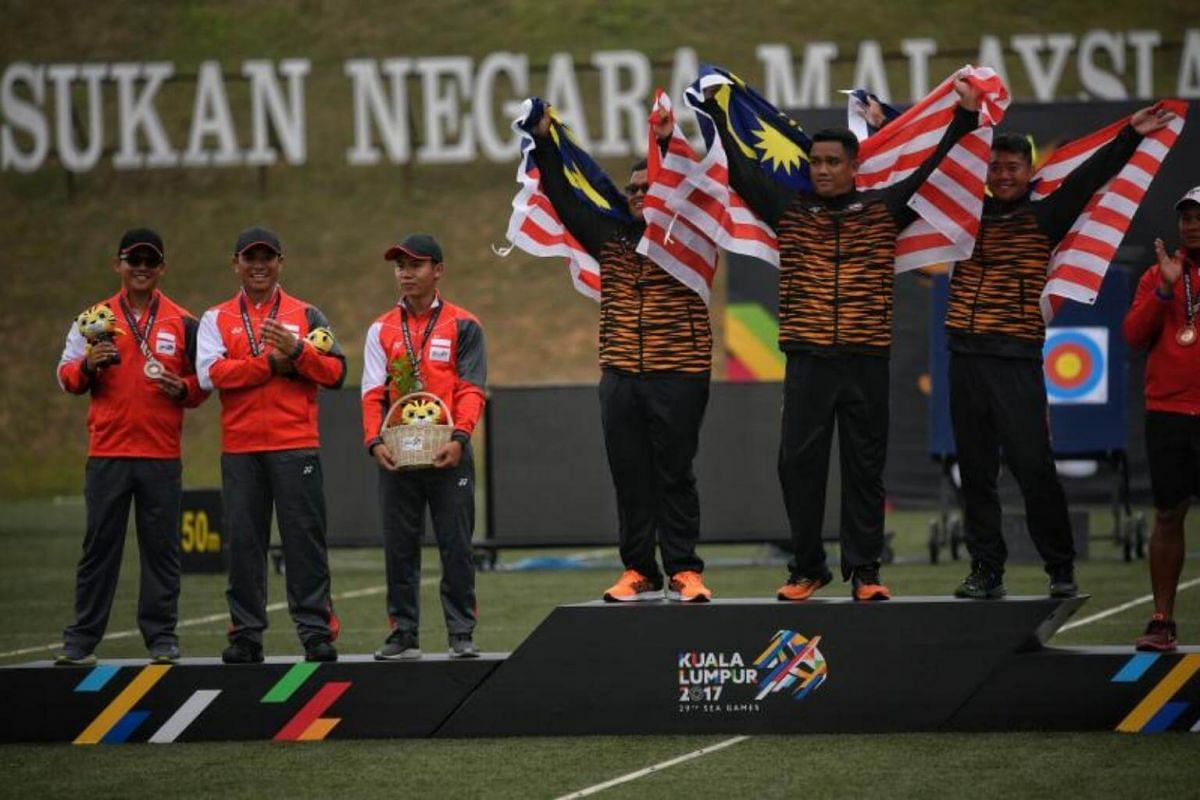 Singaporean archers (from left) Pang Toh Jin, Alan Lee and Ang Han Teng stand on the podium after receiving their silver medals at the SEA Games compound men's team event on Aug 17, 2017.
