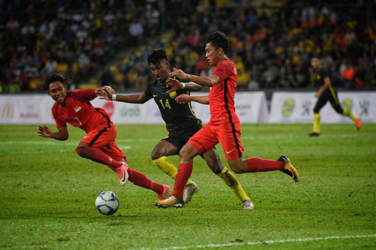 Singapore's Muhammad Muhaimin Bin Suhaimi (left) and Muhammad Syahrul Bin Sazali (right) vie for the ball with Mohamed Syamer Bin Kutty Abba during the SEA Games football match between Singapore and Malaysia on Aug 16, 2017.