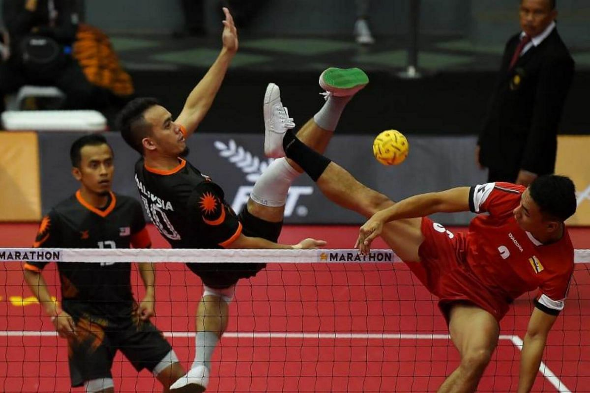 Malaysia's Mohd Hanafiah (centre) hits the ball past Mohd Aliffuddin Jamaludin (right) of Brunei during their men's Sepaktakraw team Regu round-robin match of the 29th Southeast Asian Games (SEA Games) at the Titiwangsa stadium in Kuala Lumpur on Aug