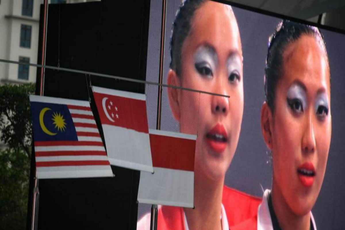 Miya Yong (left) and Debbie Soh of Singapore in pictured on a giant screen as they sing the national anthem of Singapore after their gold medal-winning duet technical routine on Aug 18, 2017.
