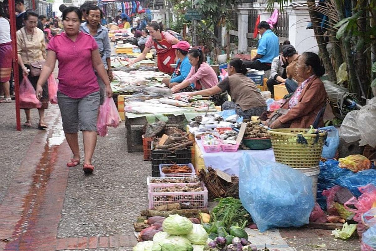 1. The morning market in Luang Prabang; 2. The aquamarine pools of Tat Kuang Si waterfall; 3. The jungle village of Ban Bor, known for its weaving tradition. The former Royal Palace, now a museum, in the Unesco World Heritage site of Luang Prabang.
