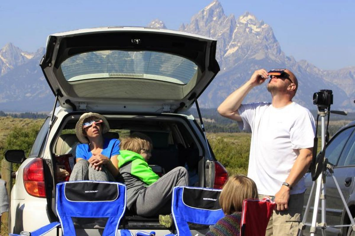 A family viewing the solar eclipse in the first phase of the total eclipse in Grand Teton National Park on Aug 21, 2017, outside Jackson, Wyoming.