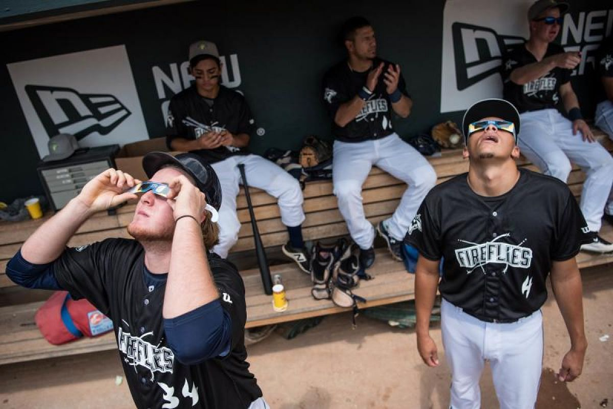 Minor league baseball players Dash Winningham (left) and Justin Brantley (right), with the Columbia Fireflies, watch the solar eclipse at Spirit Communications Park on Aug 21, 2017, in Columbia, South Carolina.