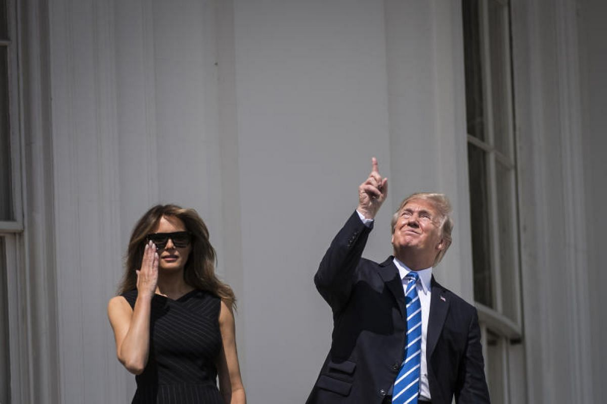 American President Donald Trump looking up towards the solar eclipse, with First Lady Melania Trump by his side, from a balcony at the White House.