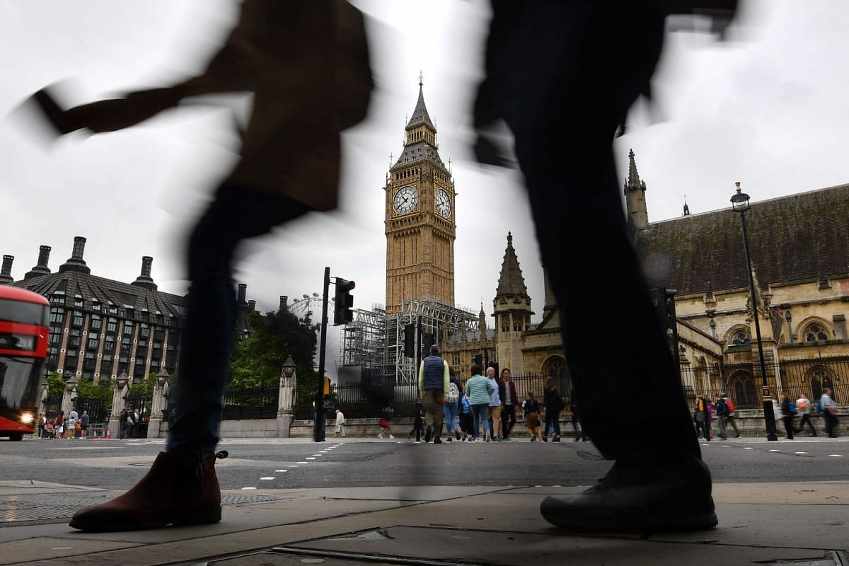 Pedestrians walk through Parliament Square at the Houses of Parliament in London on August 21, 2017 past Elizabeth Tower and Big Ben ahead of the final chimes of the famous bell before renovation works begin. Britain's Big Ben bell fell silent on Aug