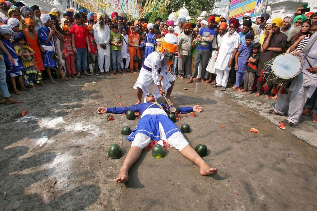 A Sikh man with his eyes covered by a cloth breaks watermelons closely placed around performer as they practise Gatkha, a traditional form of martial art, during celebrations to mark the 413th anniversary of the installation of the Guru Granth Sahib,