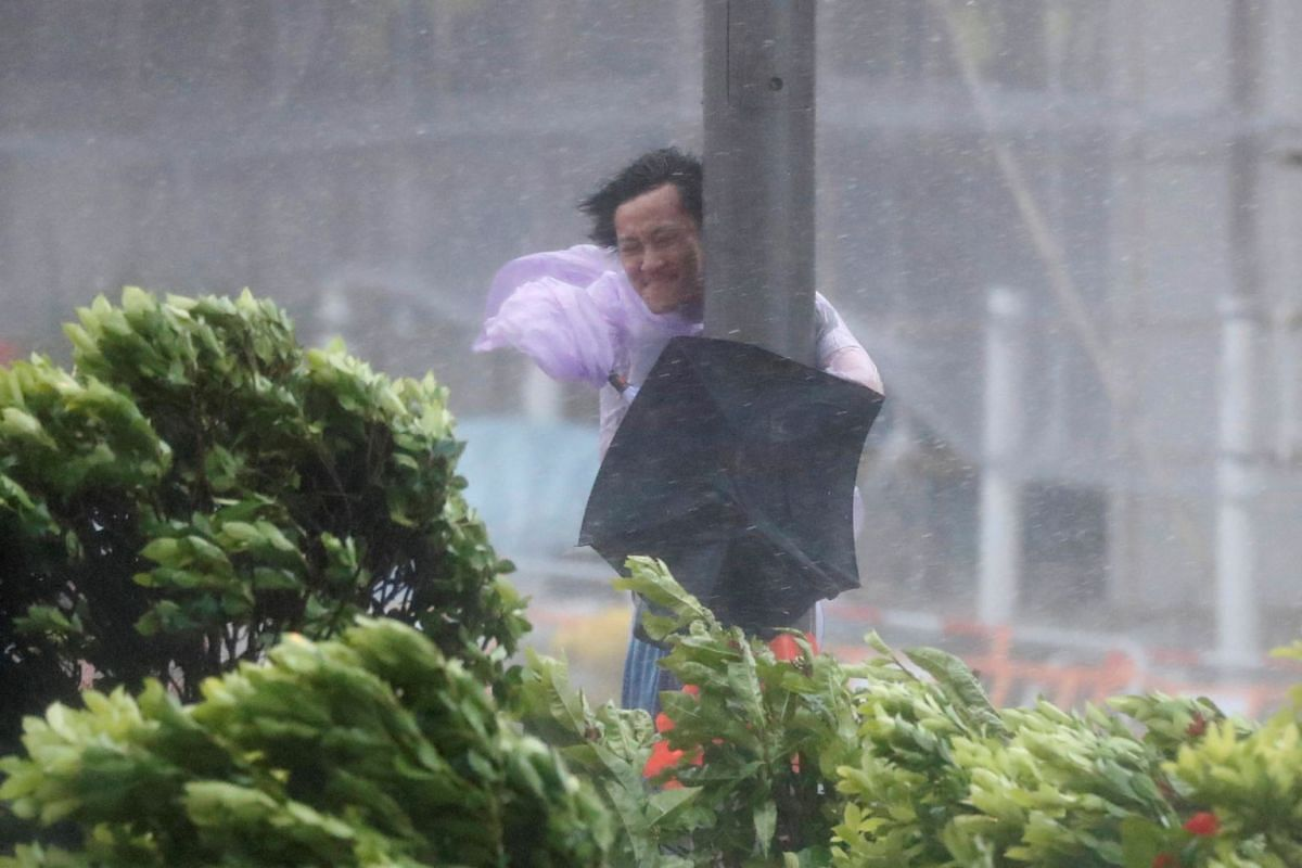 A man holds onto a lamp post against strong wind as Typhoon Hato hits Hong Kong, China August 23, 2017.
