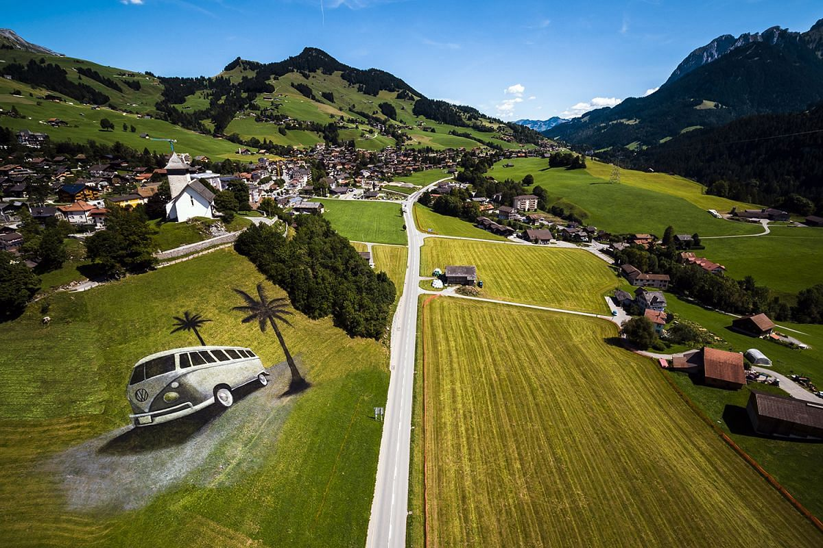 An aerial image taken with a drone showing French artist Saype's land-art painting of a Volkswagen (VW) bus on a hill in Chateau d'Oex, Switzerland, on Aug 23, 2017. The artwork, covering approximately 4200 sq m, was produced with over 400 litres of