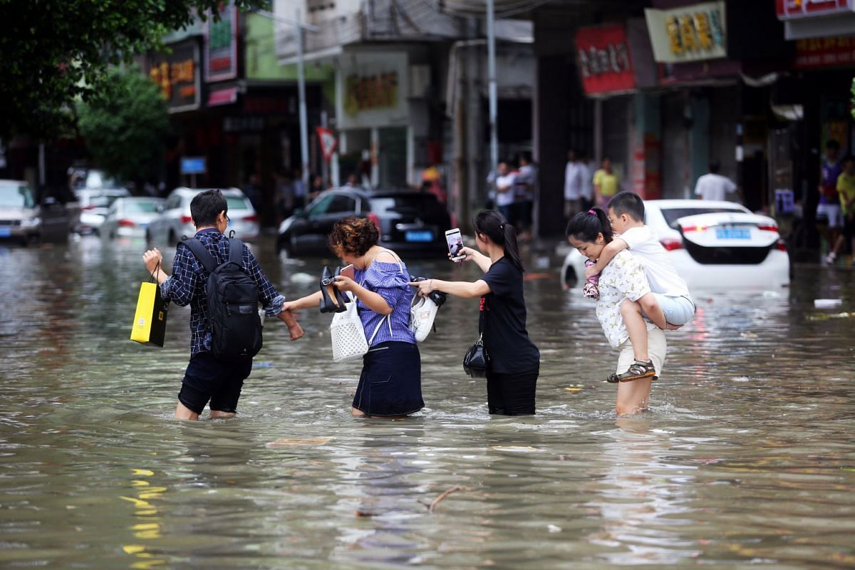 People wading through a flooded street after Typhoon Hato hit Dongguan in China's Guangdong province on Aug 23, 2017.