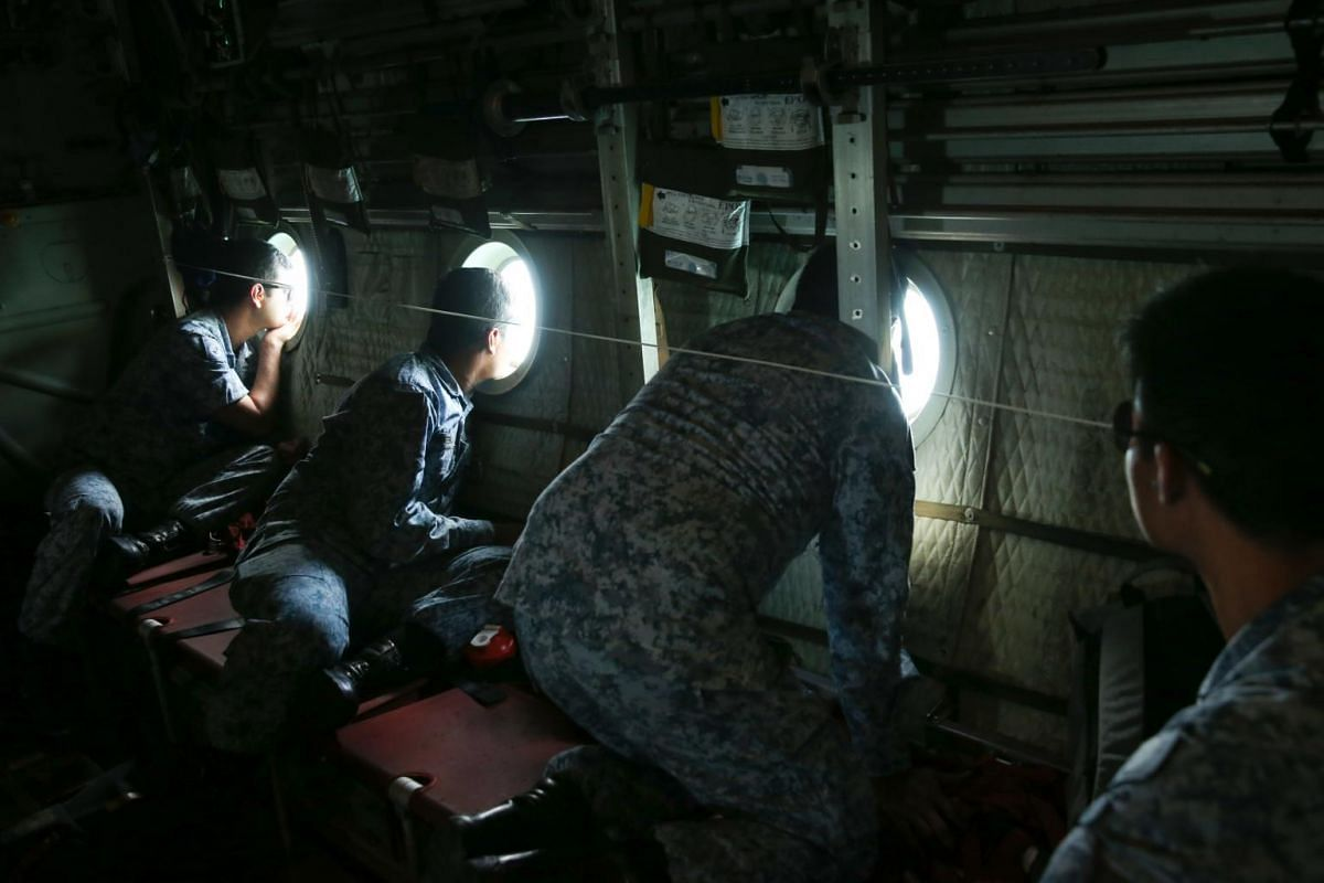 Scanners looking out for survivors and bodies through the windows on board a C-130 flying over the South China Sea, in search of missing sailors from the USS John S. McCain, on Aug 23, 2017.