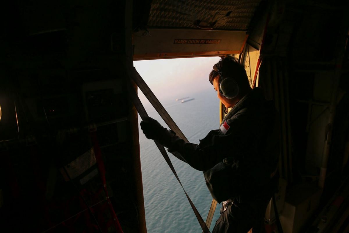 An air crew specialist from 122 Squadron on board the C-130 looking out for survivors or bodies, in Day Three of the search efforts on Aug 23, 2017.