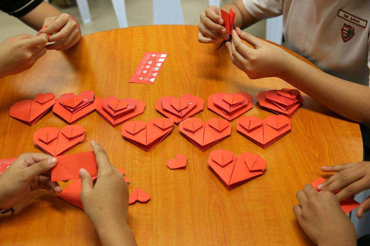 Pupils at Xishan Primary School folding red paper hearts of different sizes on Aug 24, 2017, to support the Fold-a-Heart project, where for every heart contributed, HSBC will donate $1 to the Straits Times School Pocket Money Fund.