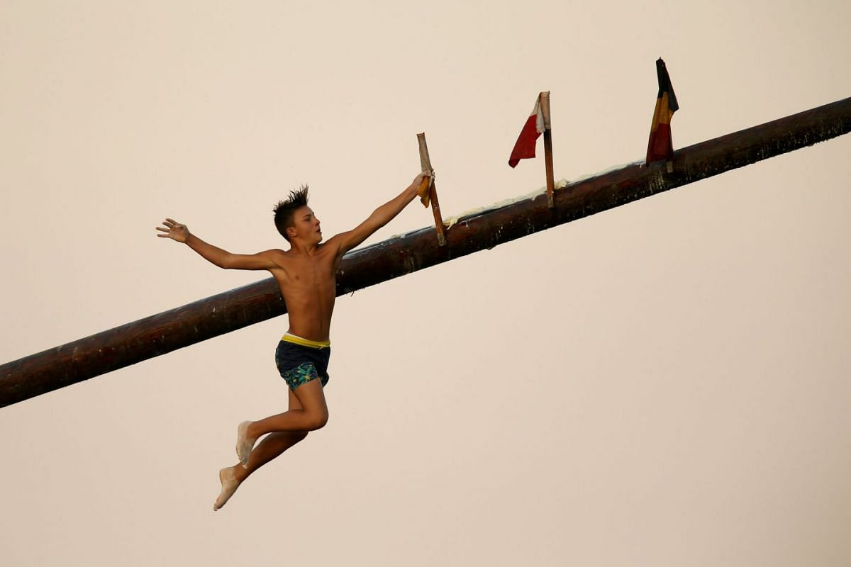 """A child competitor grabs a flag as he falls off the """"gostra"""", a wooden pole covered in lard, during the celebrations for the religious feast of St Julian, patron of the town of St Julian's, Malta, August 24, 2017. In the traditional """"gostra"""", a game"""