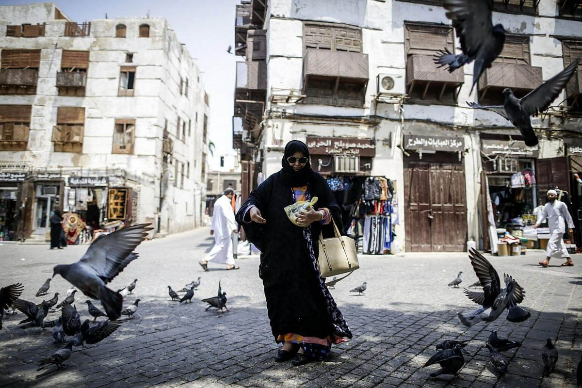A Saudi woman feeds pigeons at Balad market in the old city of Jeddah, Saudi Arabia, on Aug 27 2017.