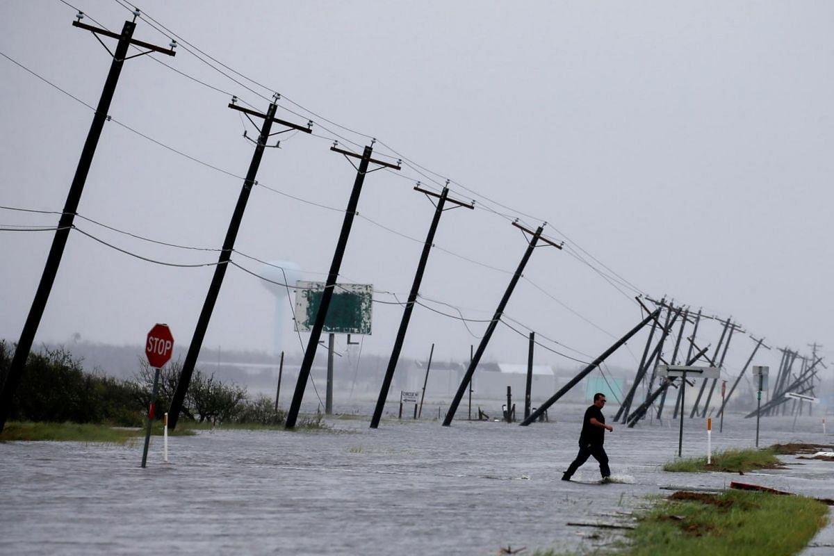 A man walks through floods waters and onto the main road after surveying his property which was hit by Hurricane Harvey in Rockport, on Aug 26, 2017.