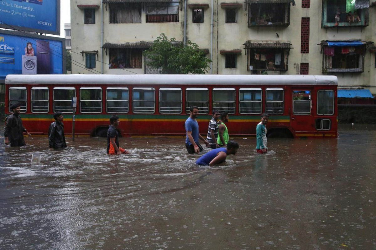 People wade through a flooded road past a stalled passenger bus during rains in Mumbai, India, on Aug 29, 2017.