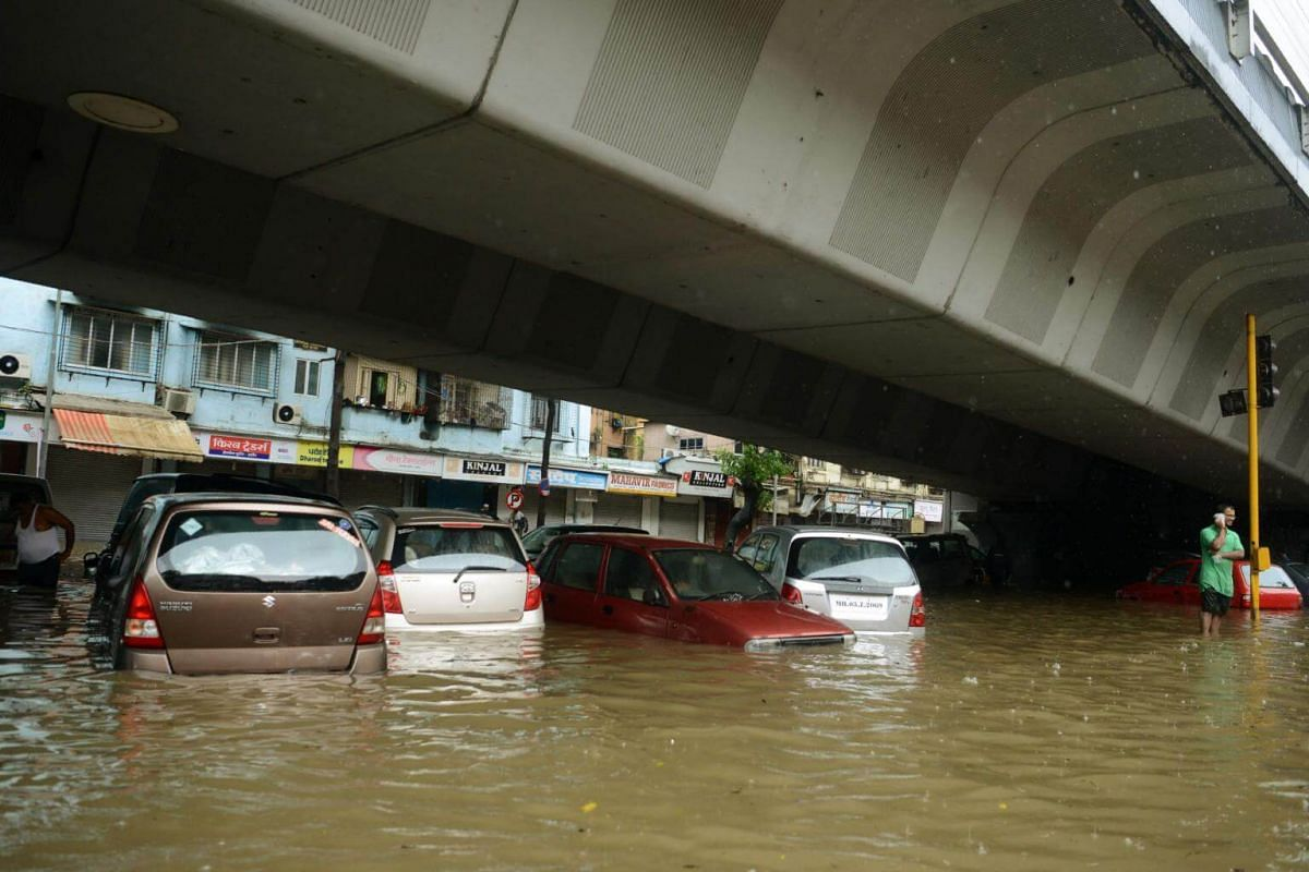 Partially submerged cars are seen along a flooded road during heavy rain in Mumbai, on Aug 29, 2017.