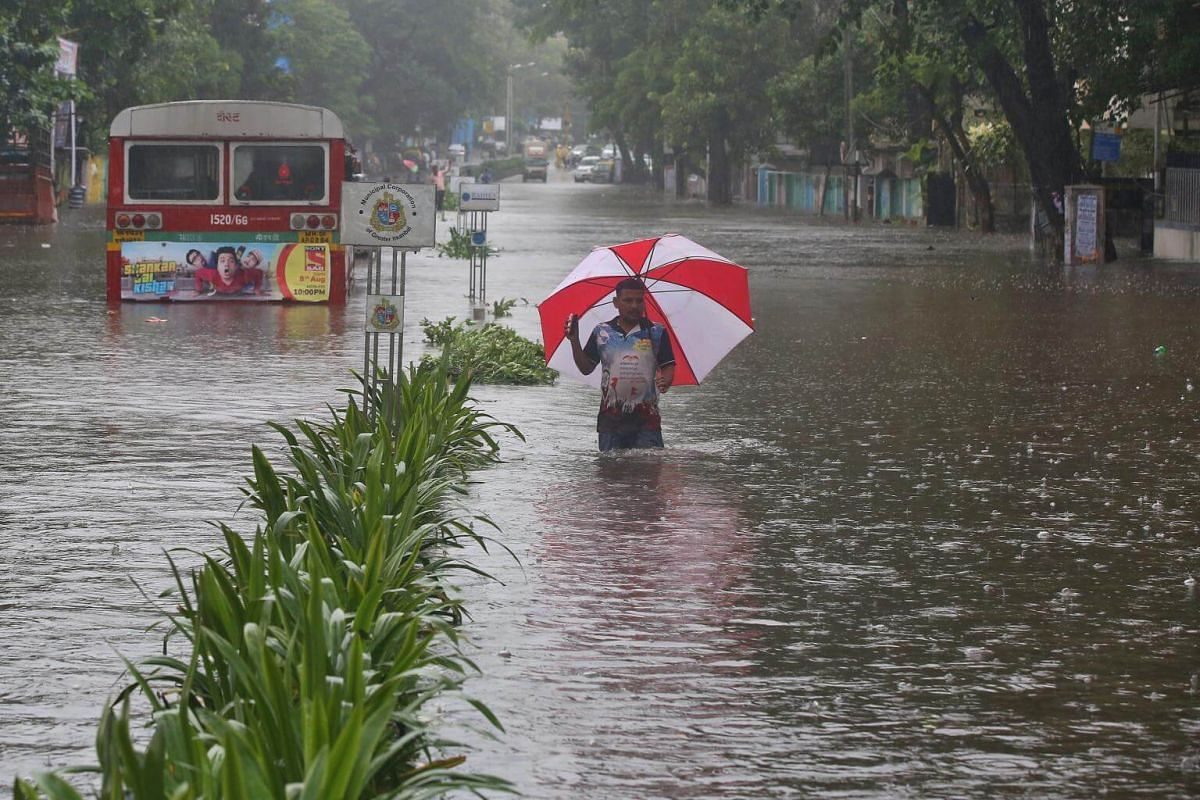 A man wades through a flooded road during rains in Mumbai, India, on Aug 29, 2017.