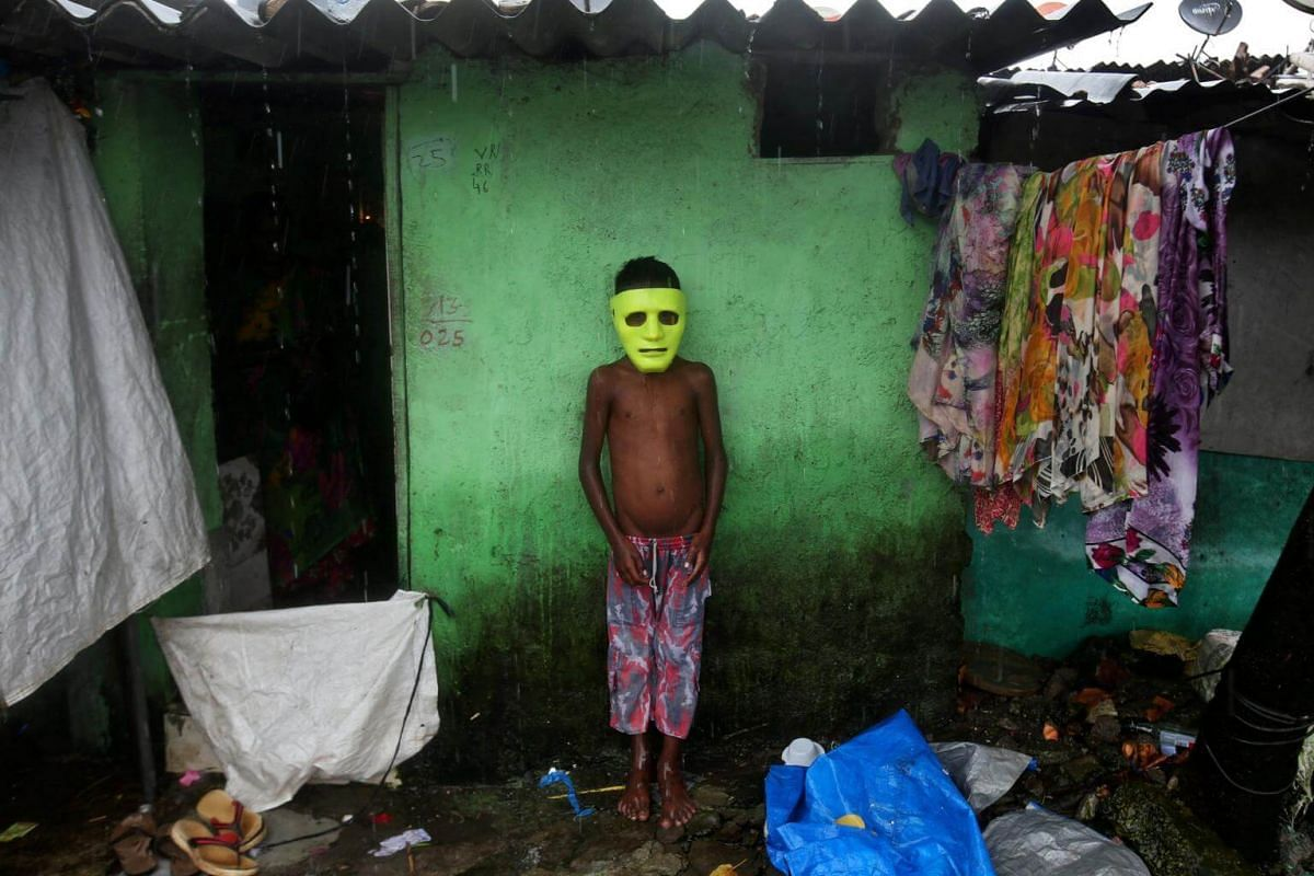 A boy takes shelter from the rain outside his house at a slum in Mumbai, India, on Aug 28, 2017.