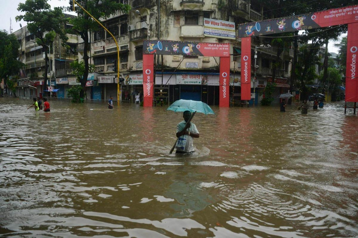 A man holding an umbrella wades through a flooded street during heavy rainstorms in Mumbai on Aug 29, 2017.