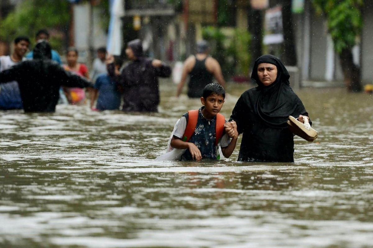 A woman wades with her son through a flooded street during heavy rainstorm in Mumbai on Aug 29, 2017.