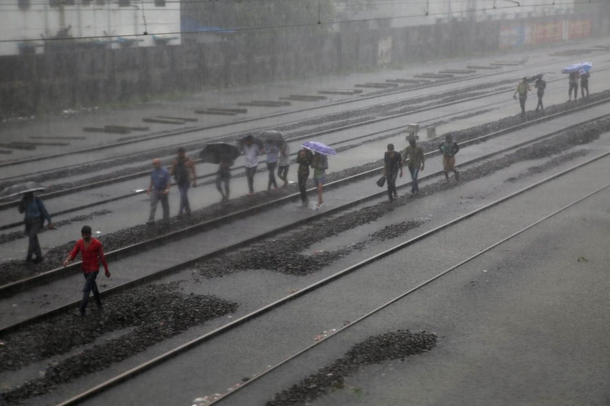 People walk on flooded railway tracks during a rainstorm at a railway station in Mumbai, India, on Aug 29, 2017.