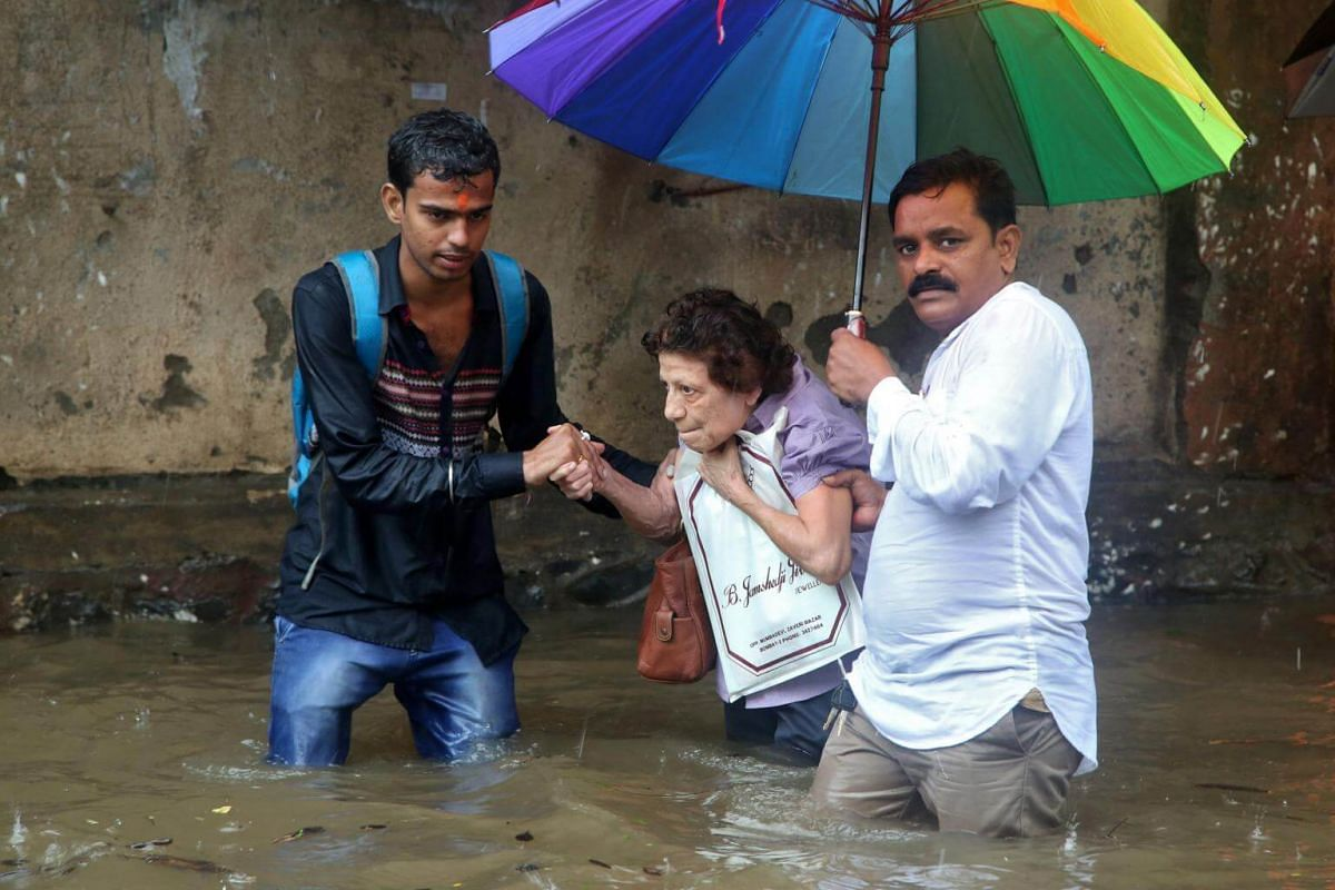 A woman is helped through a flooded road after rains in Mumbai, India, on Aug 29, 2017.