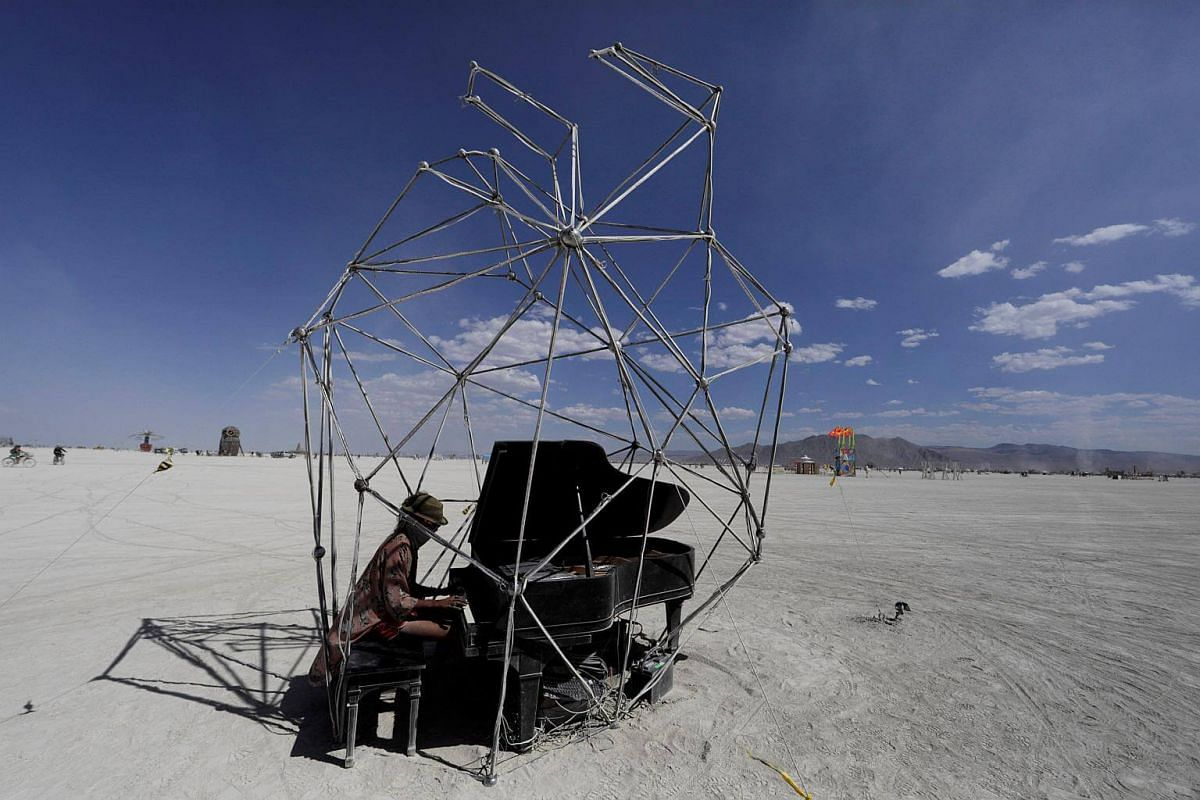 Burning Man participant Cole Wardley of Salt Lake City plays the Baby Grand piano inside the Heardt art project at the annual Burning Man arts and music festival in the Black Rock Desert of Nevada.