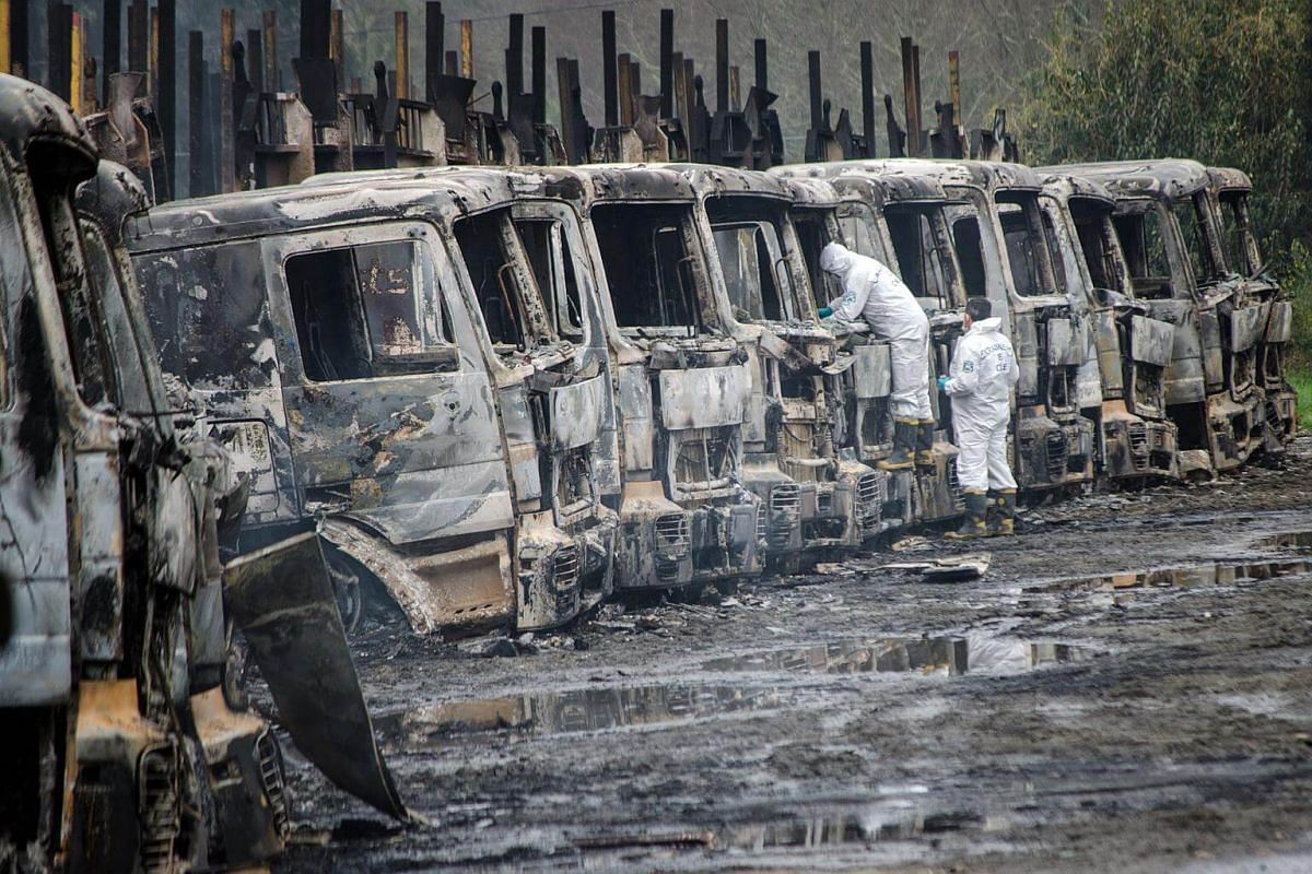 Forensic police officers collect evidence at the site where 29 trucks were burned, in San Jose de la Mariquina.