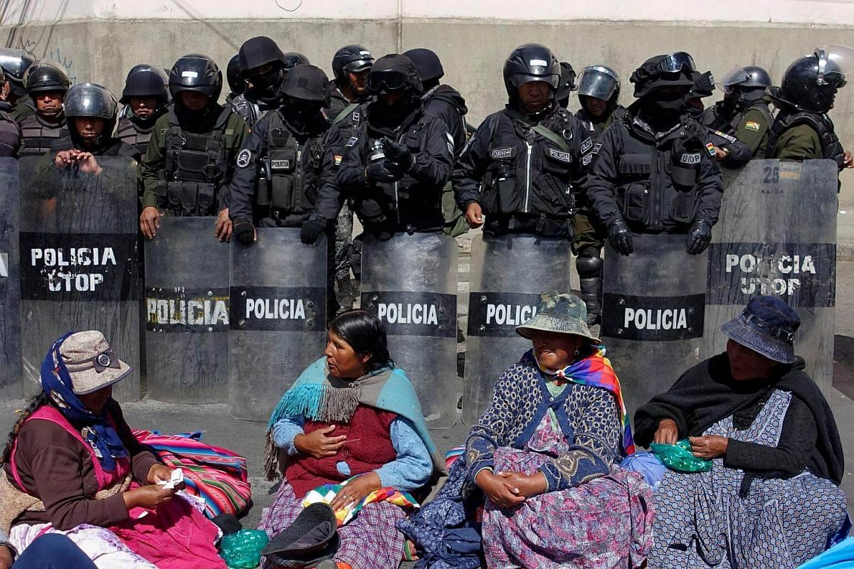Demonstrators from Achacachi rest in front of riot policemen as they take part in a protest in La Paz.
