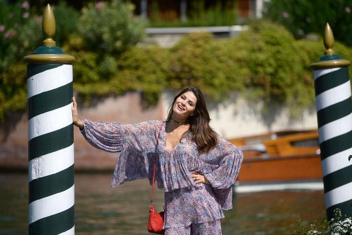 Brazilian model Isabeli Fontana poses for photographers as she arrives at the Excelsior Hotel during the 74th Venice Film Festival on Aug 30, 2017 at Venice Lido.