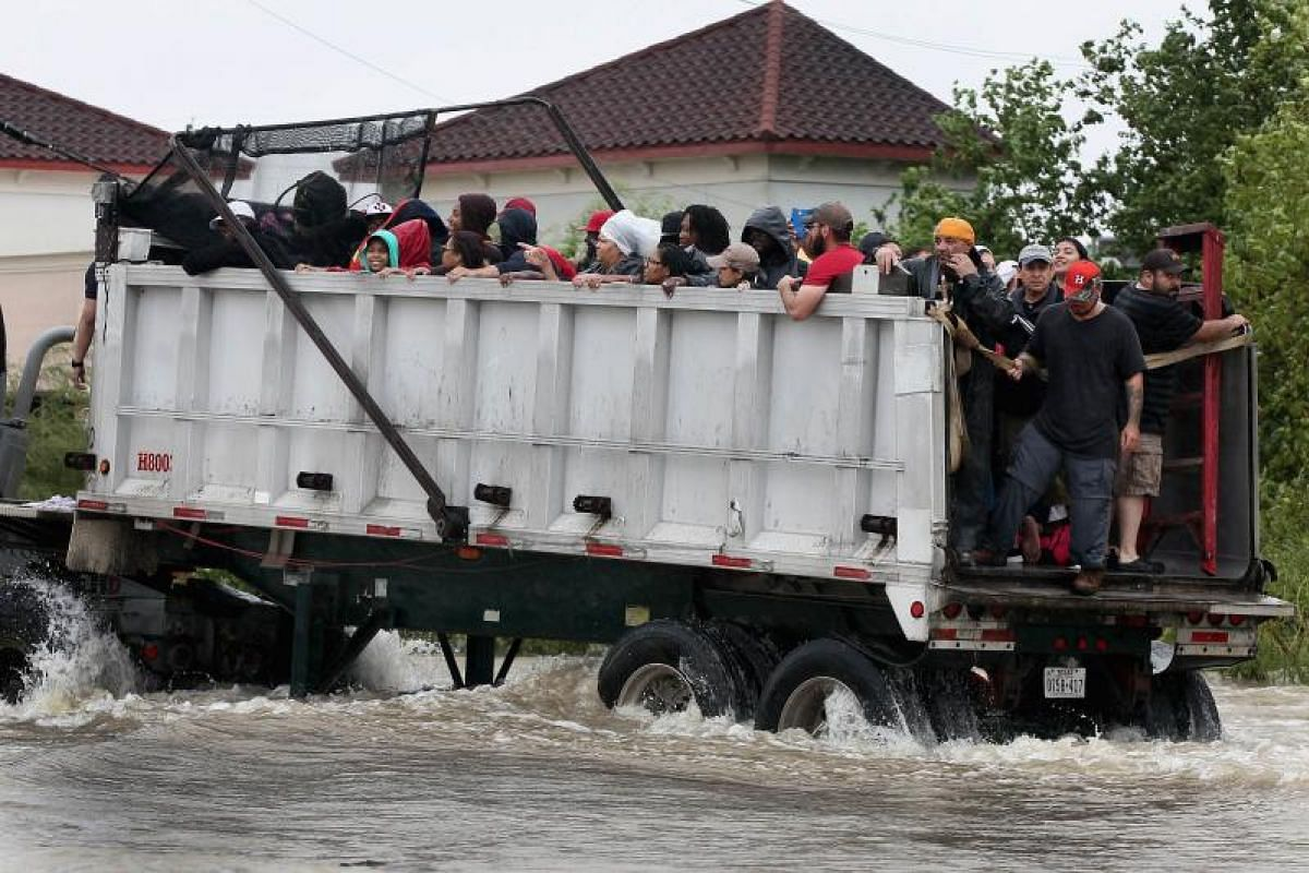 Rescue workers helping residents to get out of a flooded neighbourhood in Houston, Texas, on Aug 29, after the area was inundated with rain water following Hurricane Harvey.
