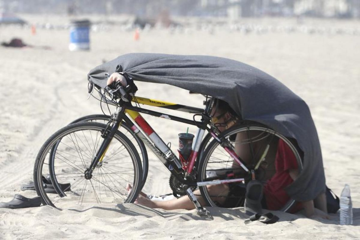 A man seeking relief from a heat wave with an improvised tent on Venice beach in California, the United States, on Aug 29.