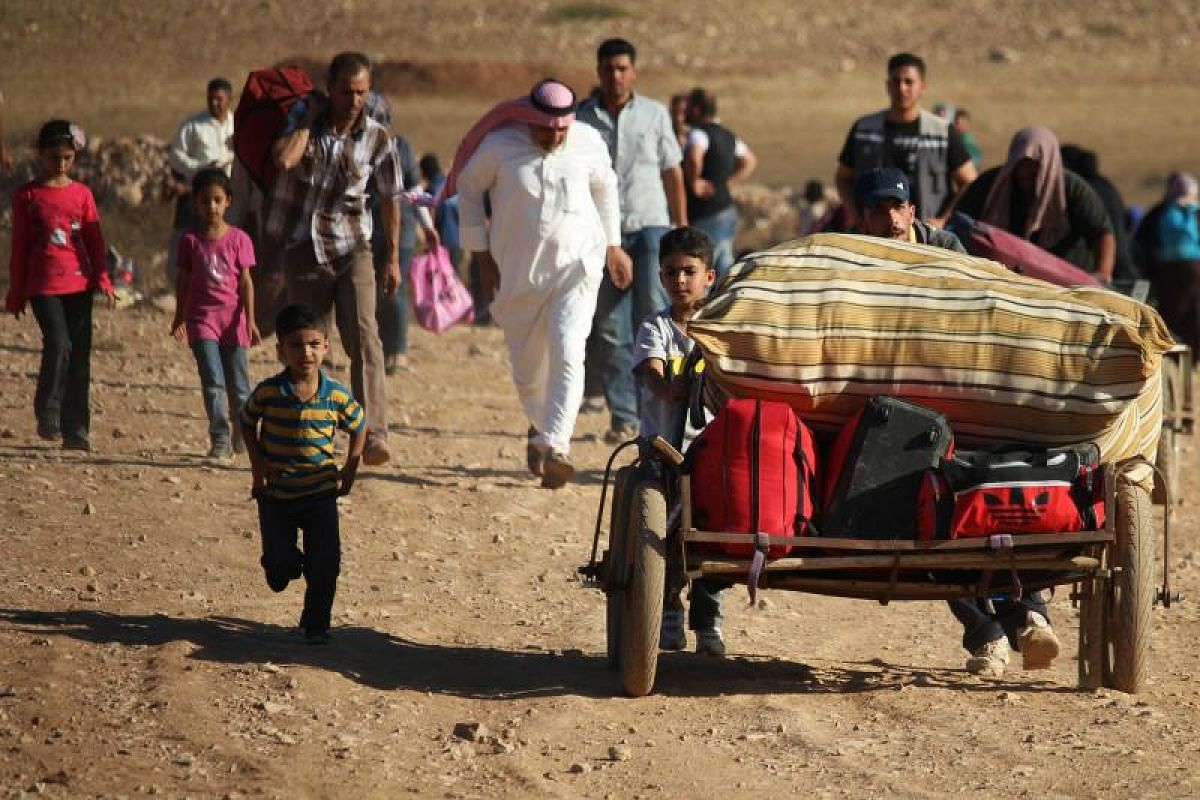 """Syrian refugees returning home to Syria after crossing the Jordanian border near the town of Nasib, in the southern province of Daraa, on Aug 29. The United States, Russia and Jordan reached a ceasefire and """"de-escalation agreement"""" for south-western"""