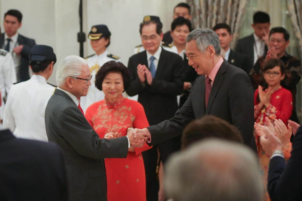 Dr Tony Tan shakes hands with Prime Minister Lee Hsien Loong as Mrs Mary Tan looks on.