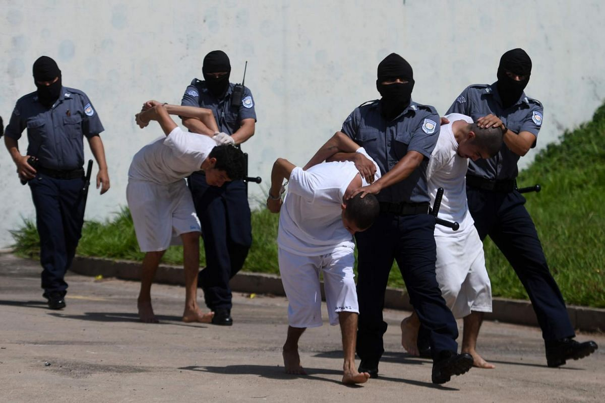 Handcuffed inmates, members of MS-13 and Barrio 18 gangs, are escorted upon arrival at the maximum security prison in Zacatecoluca, 65 km east of San Salvador, on Aug 30, 2017.