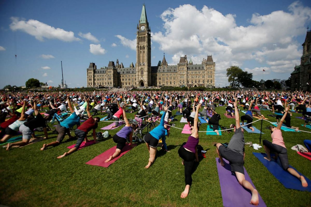 People take part in a weekly yoga class on the front lawn of Parliament Hill in Ottawa, on Aug 30, 2017.