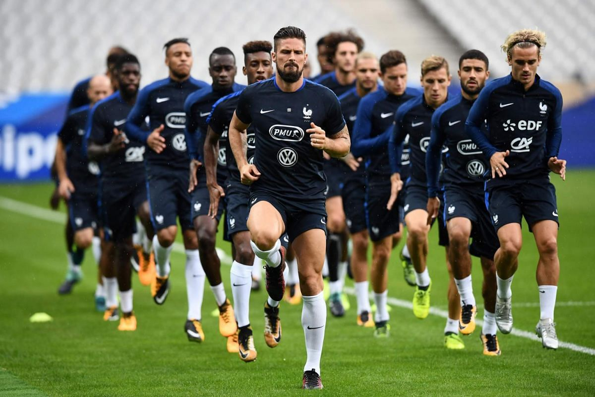 France's forward Olivier Giroud (center) and France's forward Antoine Griezmann (right) run with teammates during a training session on Aug 30, 2017.