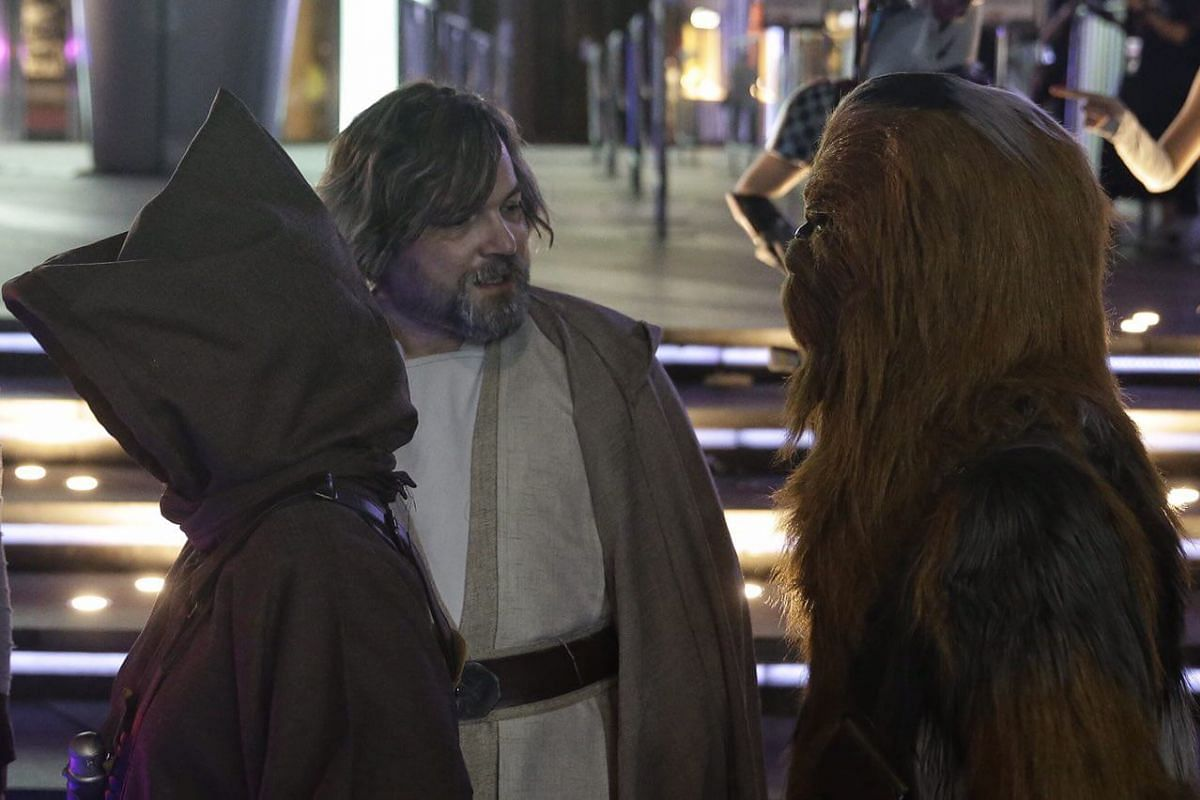 A Luke Skywalker impersonator in discussion with  a scaled-down Chewbacca outside ION Orchard.