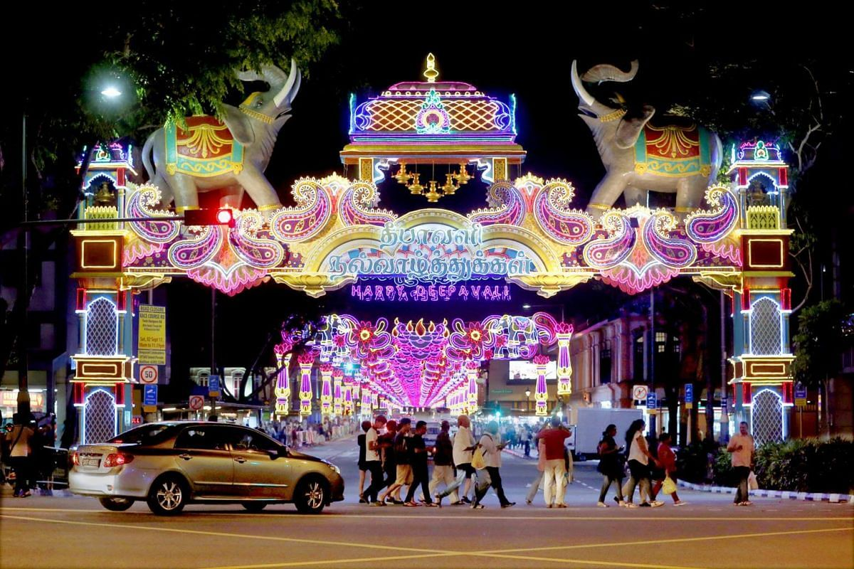 People cross the street in front of two elephants in this year's Deepavali street light-up.